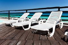 Luxury sunbeds on wooden floor near swimming pool - stock photo