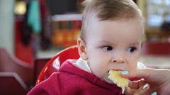 Footage little boy sitting on children's chair and eats bread Stock Footage