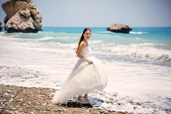 Outdoor portrait of young beautiful woman bride in wedding dress on beach. Petra Kuvituskuvat