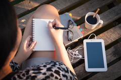 Young woman writing journal - stock photo