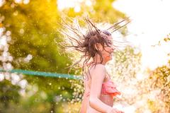 Girl in bikini dancing at the sprinkler, summer garden - stock photo