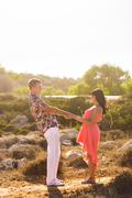 Young couple holding hands and looking at each other on sunny summer day Stock Photos