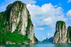 Rock islands near floating village in Halong Bay - stock photo