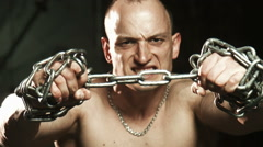 Young bald man trying to thorn the metal chain - stock footage
