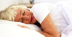 Mature woman being a restless sleeper - stock footage