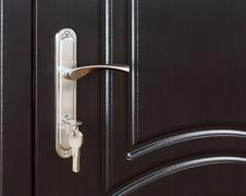 Closed dark brown wooden door handle with lock Stock Photos