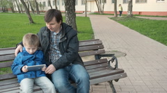 Father teaching his cute young son to use a tablet - stock footage