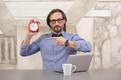 Businessman holding alarmclock Stock Photos