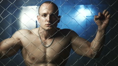 Young muscular man beyond wire in jail Stock Footage