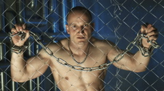 Topless man with metal chain beyond the fence - stock footage