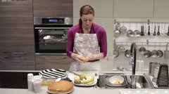 Woman cleans tangerine in the kitchen - stock footage