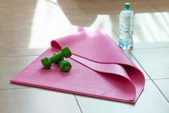 Two  dumbbells with mineral water on  yoga mat - stock photo