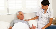 Nurse taking care of mature man lying on a bed Stock Footage