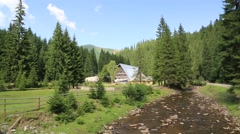 Cottage in forest near mountain river, Carpathians, Ukraine Stock Footage