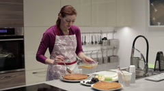 The woman smears honey on the spoon cake Stock Footage