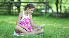Little girl in pink dress with tablet pc sits on the grass in garden Stock Footage