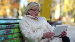 Woman sits on the bench and communicates via tablet PC Stock Footage