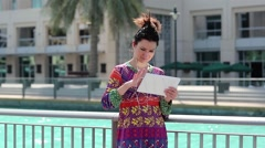 Woman with tablet computer stands near blue pool Stock Footage
