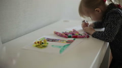 A small blond girl drawing two pictures at the same time. Slow motion Stock Footage