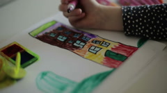 A child's hand drawing a house with a felt-tip pen. Slow motion - stock footage