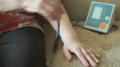 Woman measures arterial pressure using a tonometer Stock Footage