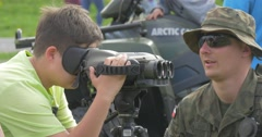 Visitors of the Exhibition of Weapons Near the Machine and Binoculars. Stock Footage