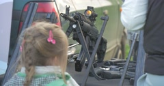 Fair-Haired Girl Looks at a Black Automatic Rifle Stock Footage