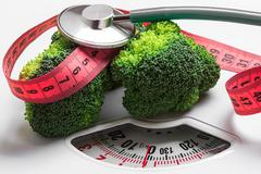 Broccoli with measuring tape on weight scale. Dieting - stock photo
