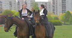 Two Women Talking While Sitting on Horseback Stock Footage
