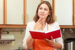 Housewife with cookbook in kitchen. Stock Photos