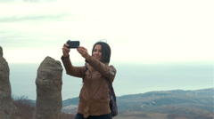 Young woman hiker taking photo with smart phone at mountain peak Stock Footage