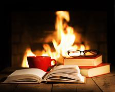 Red cup and old books on wooden table near fireplace. Stock Photos
