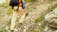 A man with a backpack walk uphill the forest trail . Stock Footage