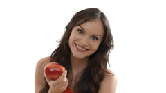 Young woman eating red apple indoors against white background Stock Footage