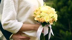 wedding bouquet of flowers in hands of the bride on green background - stock footage
