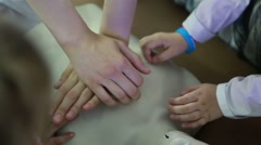 Child doing chest compressions on a mannequin Stock Footage