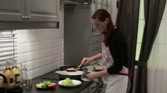 Woman puts a fish steak on a plate Stock Footage