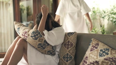 Young couple in bathrobes fighting, arguing on sofa at home Stock Footage