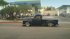 Young man driving lowered 1950s Chevy pickup truck in Los Angeles Stock Footage