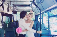 The groom kisses the bride in public transport. Blue bus Stock Photos