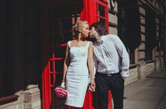 Bride and groom kissing on background of the phone booth. Tourism, travel people Stock Photos