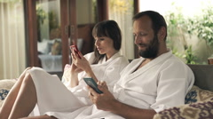 Young couple in bathrobes using smartphones sitting on sofa in outdoor villa Stock Footage