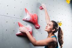 Pretty young sportswoman training at climbing - stock photo
