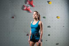 Sporty female standing in climbing equipment - stock photo