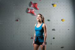 Sporty female standing in climbing equipment Stock Photos