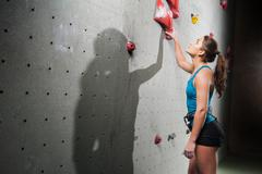 Sporty female looking up on climbing wall Stock Photos