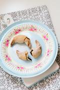 Freshly baked short crust pastry crescent rolls topped with ice sugar on a co - stock photo