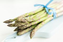 Bunch of fresh asparagus on a blue wooden cutting board Stock Photos
