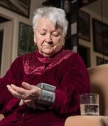 Old woman measures arterial pressure - stock photo