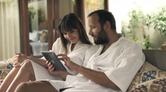 Young couple in bathrobes talking over tablet computer sitting on sofa Stock Footage